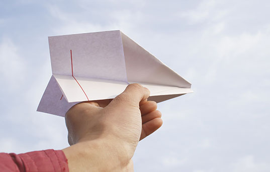Hand launching paper airplane
