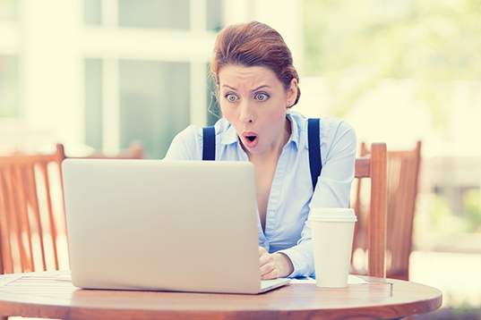 Shocked young business woman using laptop looking at computer sc