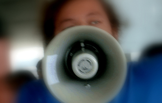 person speaking into a megaphone