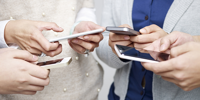 small group of people using cellphones together.